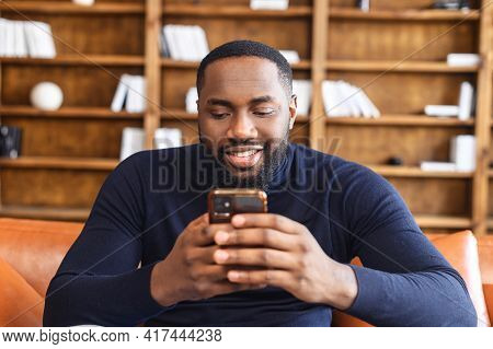 African American Unshaved Man Sitting On The Sofa, Holding Smartphone In Hands Passionate About Some
