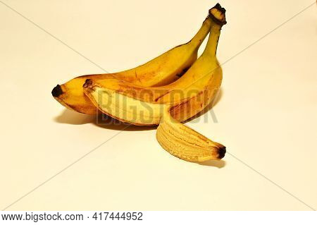 Two Bananas On A White Background On One Peeled Peel