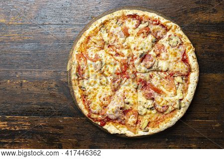 Fresh Italian Pizza With Bacon, Tomatoes, Mushrooms And Cheese On A Wooden Background.  Italian Food
