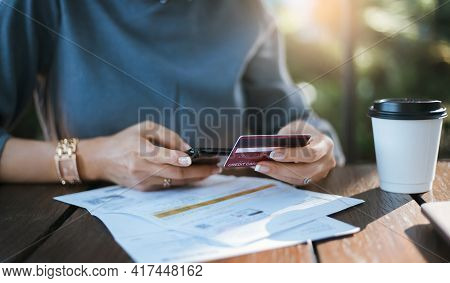 Close-up Of Young Asian Woman Using Smart Phone And Credit Card For Shopping Online And Paying Bills