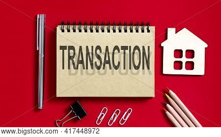 Transaction Text Written On Notebook With Pencils And Office Tools And Model Wooden House