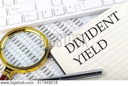 Divident Yield Text On The Notebook With Chart, Magnifier,keyboard And Pen