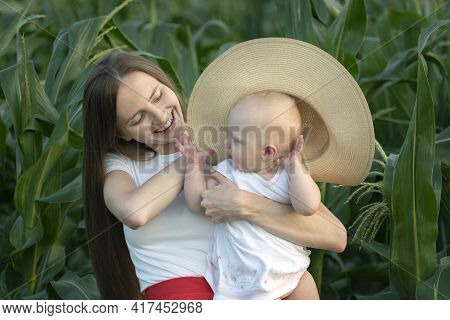 Beautiful Young Mother Holds Kid On Her Hands And Puts Him Hat. Tenderness Of Motherhood.