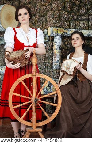 Portrait Of Two Lovely Smiling Caucasian Ladies  Posing With Spinning Wheel And Fancywork Hoop In Re
