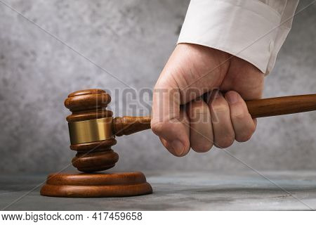 Judge Gavel In Hand Against Gray Wall Background, Sentencing Concept.