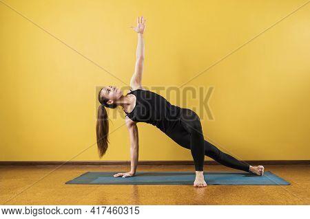 Woman Practicing Yoga, Doing Vasishthasana Exercise, Side Plank Pose, Exercising On A Mat In The Stu