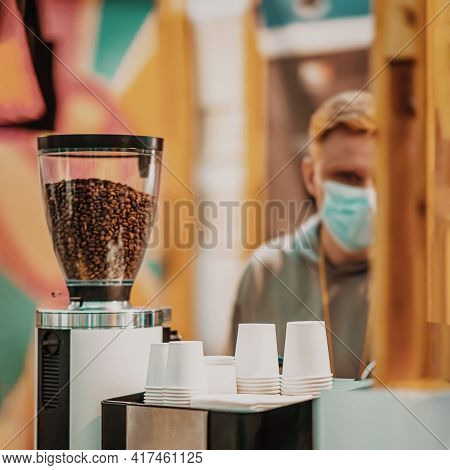 Coffee Machine With Coffee Beans And Rows Of Upside Down Paper Cups For Coffee, Blurred Background O