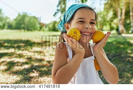 Closeup Of Happy Cute Little Girl Smiling Posing With Two Lemons, Having Fun During Sitting On The P