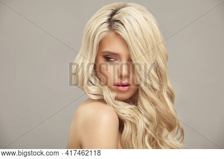 Pretty Young Blonde Woman With Nude Makeup Has A Curly Long Bright Hair, Close Up Portrait On Beige