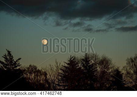 Full Moon In Horizon Of Dramatic Night Sky