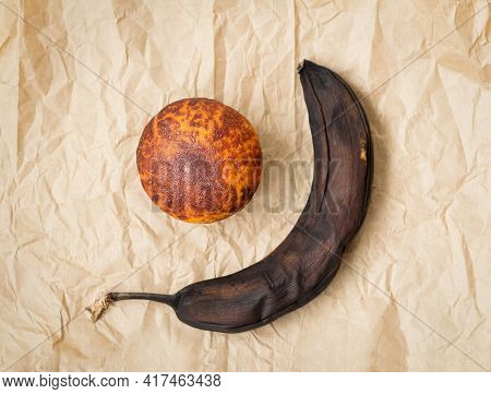 Rotten Banana And Spoiled Tangerine On Brown Crumpled Paper.