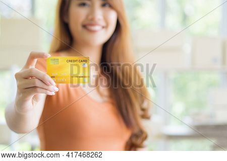 Close-up Of The Right Hand Of A Young Woman Holding A Yellow Credit Card, Seeing A Smile But Not See