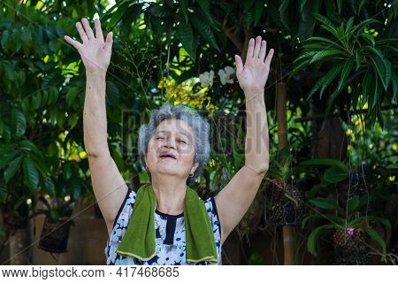 Portrait Of An Asian Senior Woman Wearing Casual Clothing, Smiling And Exercises By Gesturing Raise