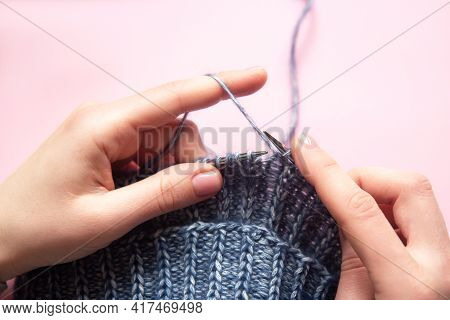 Female Hands With Knitting Needles To Knit Wool Blue Sweater On Pink Background. Woman Knitting Wool