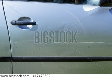A Large Scratch On The Door Of A Silver Car. Concepts- Accident, Car Insurance, Traffic Accident.