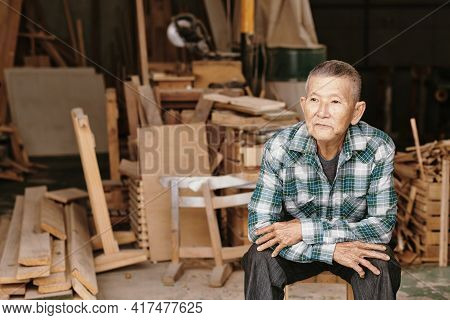 Portrait Of Pensive Experienced Senior Carpenter In Plaid Shirt Resting After Fishing Work On Big Pr