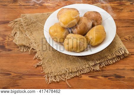 Hot Whole Potatoes Boiled In Their Jackets On The White Dish On An Old Rustic Table With Sackcloth
