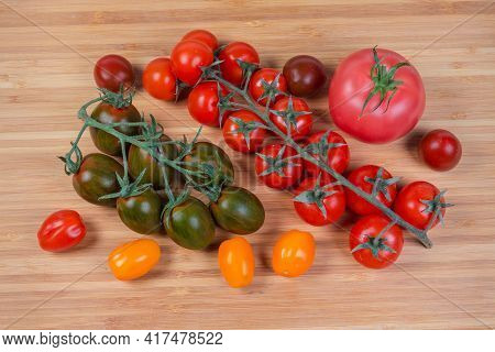 Multicolored Fresh Ripe Cherry Tomatoes On Branches And Separately, Single Ordinary Pink Tomato On A