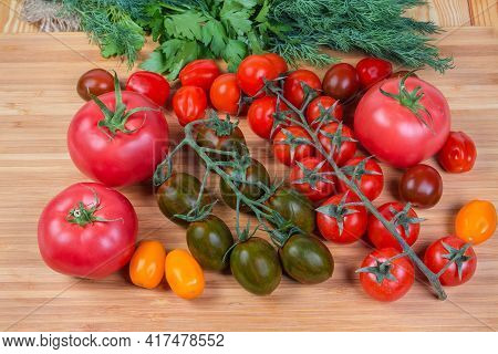 Multicolored Fresh Ripe Cherry Tomatoes On Branches And Separately, Ordinary Pink Tomatoes Against T