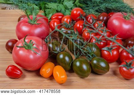 Multicolored Fresh Ripe Cherry Tomatoes And Ordinary Pink Tomatoes Against The Greens On A Wooden Cu