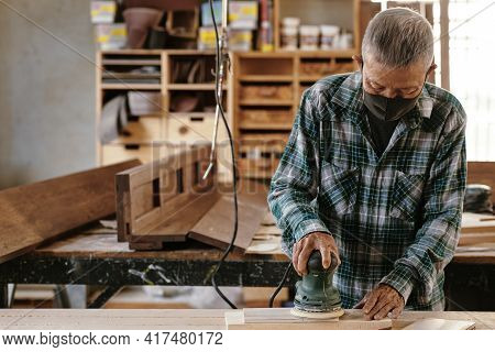 Elderly Experienced Carpenter In Protective Mask Polising Wooden Plank With Electric Sander