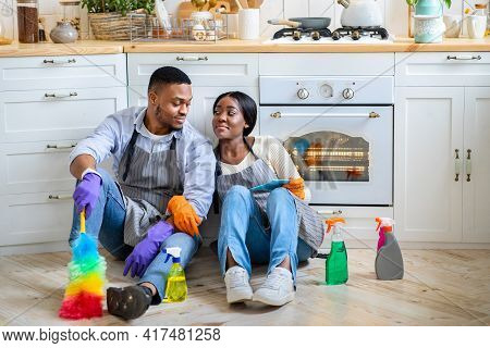 Tired Black Couple Sitting On Floor Among Cleaning Supplies After Finishing Cleanup, Looking At Each