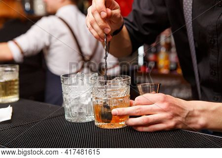 A Male Bartender Uses Spoon To Mixing Cocktail.