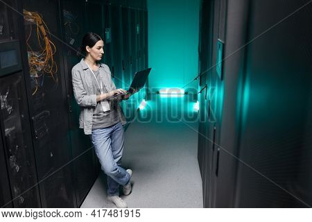 Full Length High Angle Portrait Of Female Data Engineer Holding Laptop While Working With Supercompu
