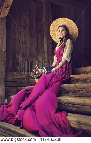 Romantic Vintage Woman In Summer Hat Dreaming With Book On Wooden Stairs Background. Victorian Fashi