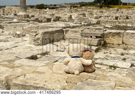Two Small Teddy Bears Sitting At Ancient Archaeological Site