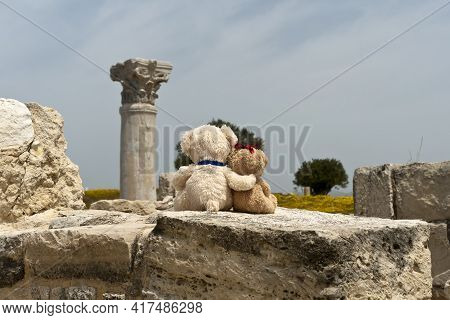 Two Small Teddy Bears Sitting On Ancient Stone Wall At Archaeological Site