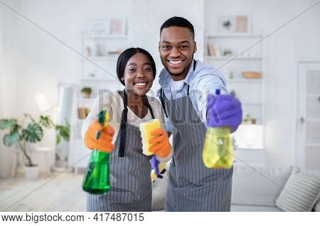 Happy Black Guy And His Wife Aiming Spray Detergents At Camera, Performing Domestic Cleanup, Indoors