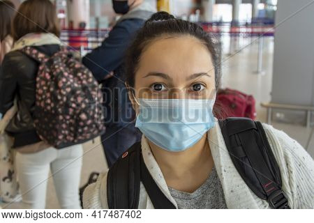 Portrait Of A 35-40-year-old Woman In A Medical Mask And Contact Lenses At The Airport, Check-in For
