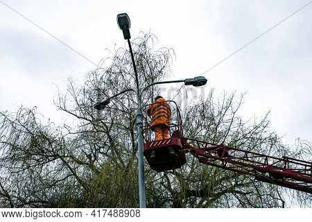 A Municipal Worker In Protective Gear Replacing Bulbs In A Street Lamp. A Worker Repairing A Street