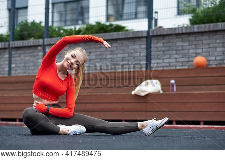 Sportswoman Doing Leg Stretching Exercise With Medicine Ball. Fit Woman Exercising With Ball In Gym
