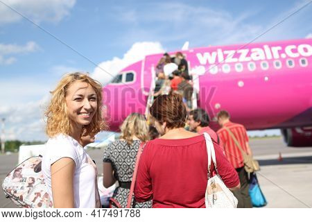 Vilnius, Lietuva, 1.09.2020 - Smiling Blonde Girl Looking At Camera On Airfield. Passengers Boarding
