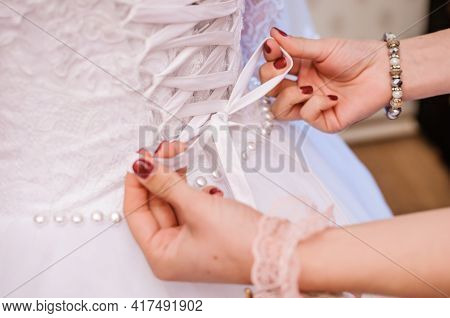 Bridesmaids Tie A Bow On The Wedding Dress. Preparing The Bride. Morning Of The Bride