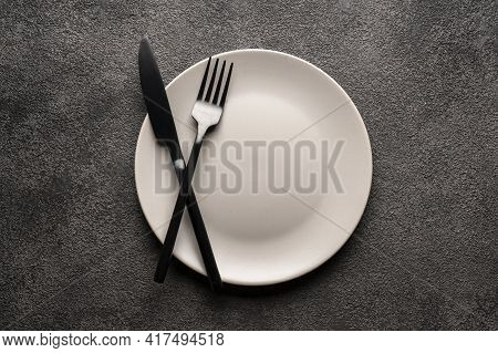 A White Empty Plate On A Gray Background And A Fork And Knife. Concept For A Restaurant Or Menu