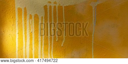 Yellow Painted Plastered Wall Background With Colorful Drips, Flows, Streaks Of Paint And Paint Spra