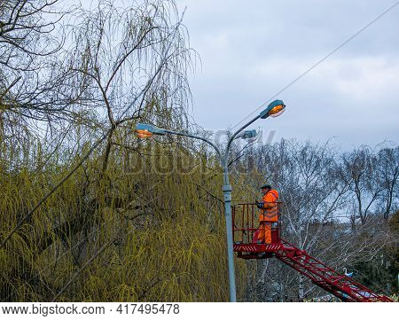 Dnepropetrovsk, Ukraine - 04.12.2021: A Municipal Worker In Protective Gear Replacing Bulbs In A Str