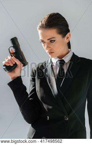 Brunette, Sensual Woman In Formal Wear Holding Handgun Isolated On Grey.