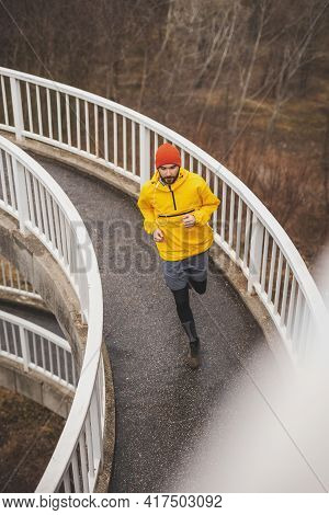 High Angle View Of An Active Man Jogging On The Bridge Pathway As Part Of Daily Morning Workout Rout