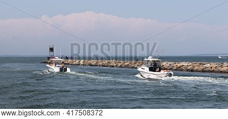 Hampton Bays, New York, Usa - 6 June 2020: Two Moter Boat Next To A Rock Jetty Entering The Great Pe
