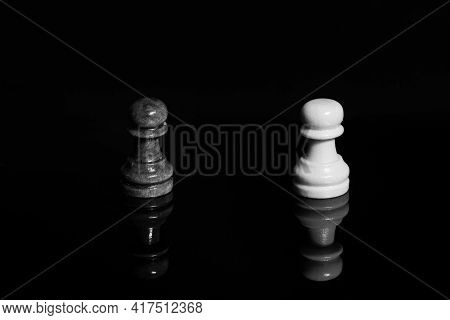 Wooden Black Pawn In Front Of White Chess Piece. Black Isolated Background With Reflection. Concept
