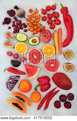 Healthy super foods high in lycopene and anthocyanins for good heart health also high in antioxidants, vitamins, minerals. omega 3 and dietary fibre. With fruit and vegetables. On mottled grey.