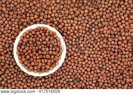 Organic dried carlin peas in a white porcelain bowl and forming an abstract background. Very high in protein, low in fat, high in fibre, antioxidants and anthocyanins. Flat lay, top view.