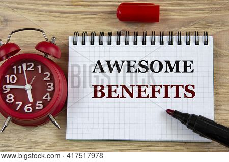 Awesome Benefits - Words In A Notebook On A Wooden Background With An Alarm Clock And A Marker. Busi