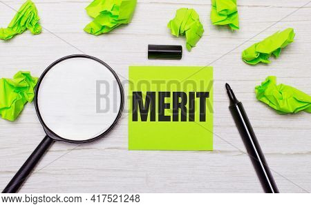 The Word Merit Written On A Green Sticky Note Next To A Magnifying Glass And A Black Marker On A Woo