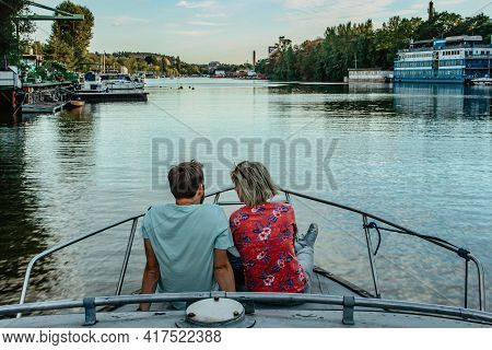 Young Happy Couple Sitting On Boat And Sailing The River.man And Woman In Love Having Romantic Date.