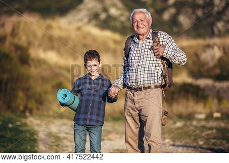 Grandfather And Grandson Holding Hands While Hiking